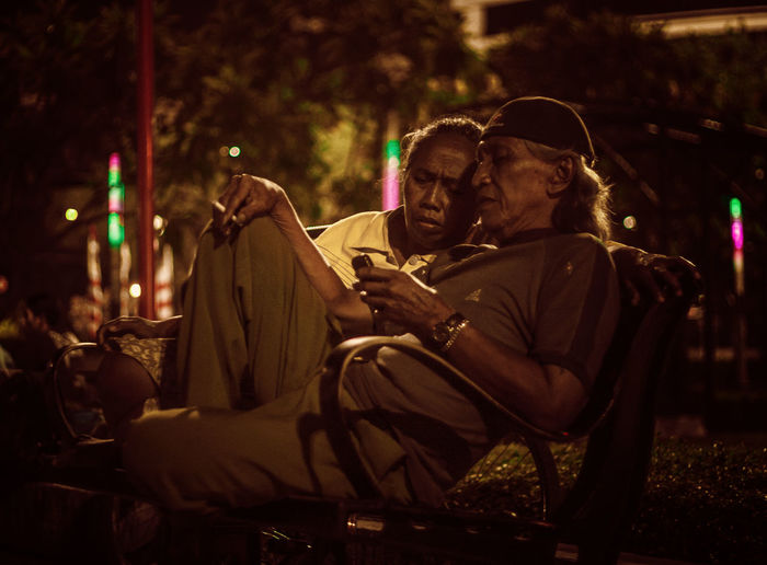 Man Using Mobile Phone By Woman While Sitting On Chair At Night