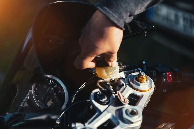 Cropped hand of mechanic repairing motorcycle