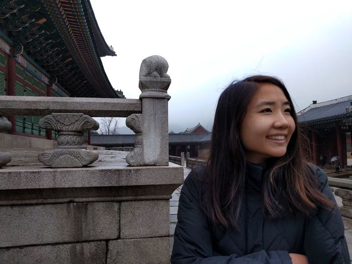 Happy young woman standing by traditional building