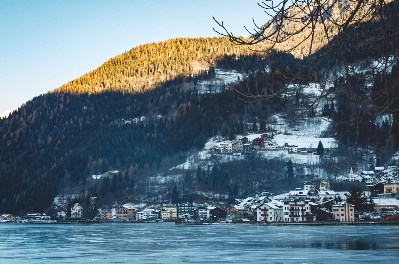 built structure, cold temperature, winter, mountain, house, snow, tree, building exterior, nature, no people, architecture, outdoors, sky, residential building, landscape, beauty in nature, water, scenics, day, view into land, city