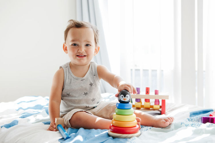 Cute boy playing with toy on bed