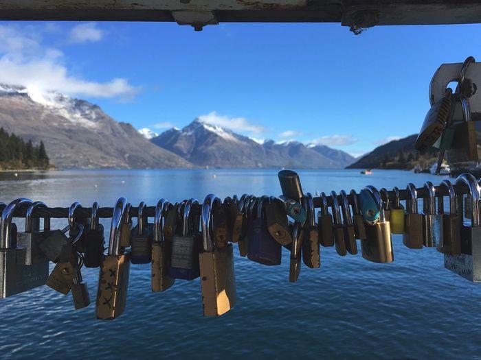 Panoramic view of padlocks hanging on mountain against sky