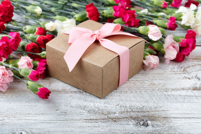 Gift box with colorful carnations in background on white weathered wooden boards Easter Giftbox Holiday Love Wood Carnation Flowers Close-up Gift Mothers Day Springtime