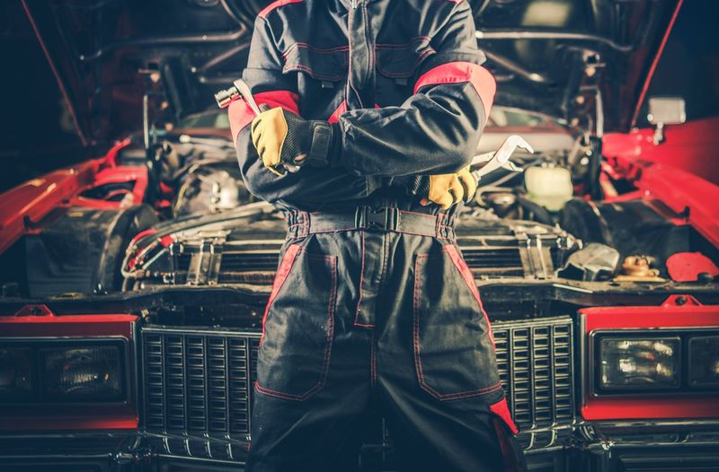 Midsection of mechanic with arms crossed standing by car in workshop