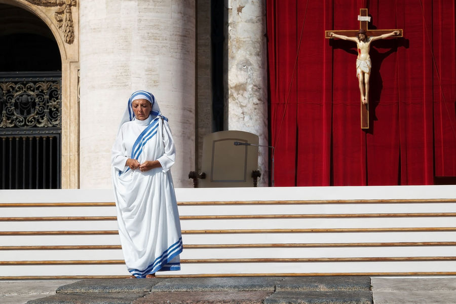 VATICAN - September 3, 2016: A nun prays in the churchyard of St. Peter's Basilica, during the celebrations of the canonization of Mother Teresa of Calcutta. Behind him stands a large crucifix on a red background. Arch Architecture Building Exterior Built Structure Cross Day Façade Jesus Christ Nun Outdoors Person Prays Religius Sister Vatican