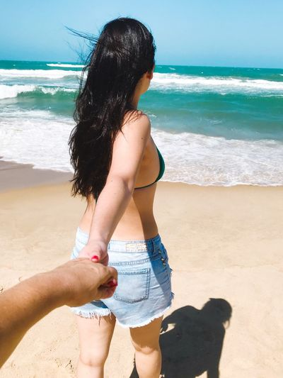 Close-Up Of Man Holding Hand Of Woman At Beach Against Sky