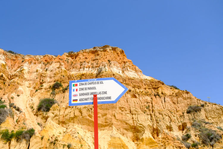 Low angle view of information sign on rock against clear blue sky