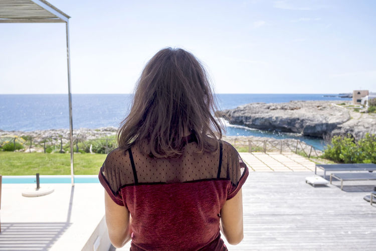 Rear view of young woman standing on the terrace looking away to the sea horizon in a sunny day Rear View Water Sea Sky One Person Women Nature Hairstyle Leisure Activity Long Hair Adult Day Holiday Hair Horizon Lifestyles Vacations Trip Sunlight Horizon Over Water Outdoors Looking At View Swimming Pool