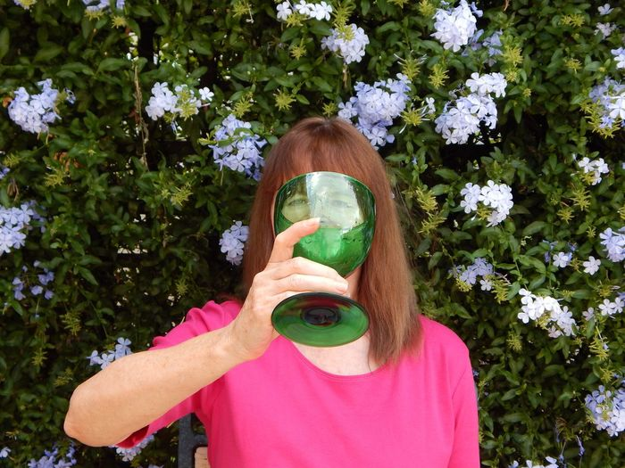 Portrait of woman holding large green glass against flowering plants