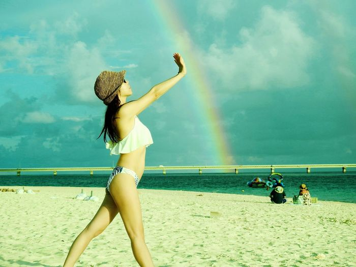 Side view of woman standing against rainbow at beach