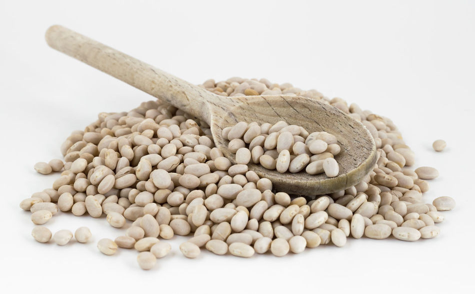 Heap of navy beans with wooden spoon on white background. Shallow DOF. Agricolture Beans Diet Dried Eating Food Healthy Heap Ingredient Legume Maximum Closeness Navy Nutrition Organic Phaseolus Vulgaris Protein Raw ShareTheMeal Small Spoon Vegan Vegetarian Vulgaris Wood Wooden