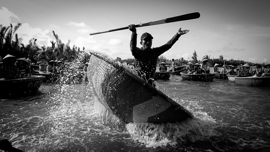 Man surfing on boat in water against sky