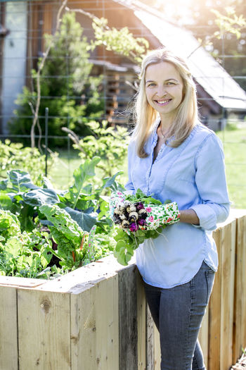 Portrait of mid adult woman holding radishes at farm