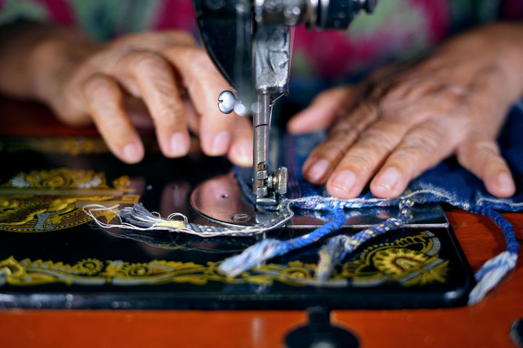 Cropped image of woman using sewing machine