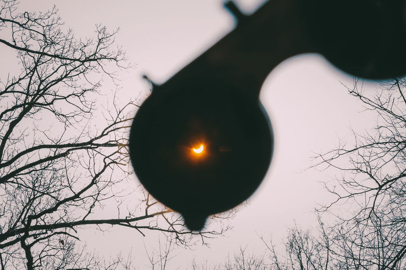 Close-up of silhouette eyewear against solar eclipse