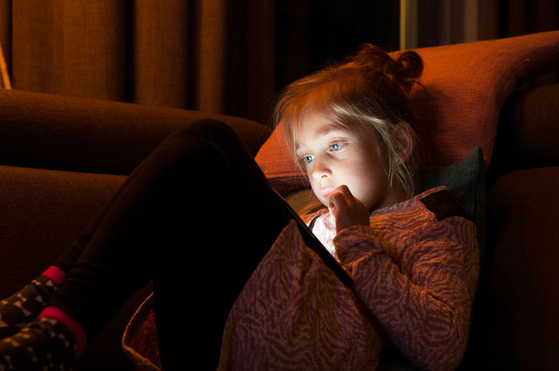 Portrait Of Girl Using Digital Tablet On Sofa