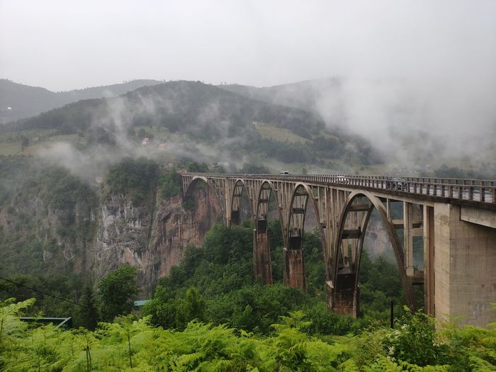 Arch bridge over mountains against sky