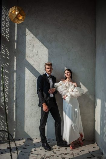 Full length of couple standing against the wall