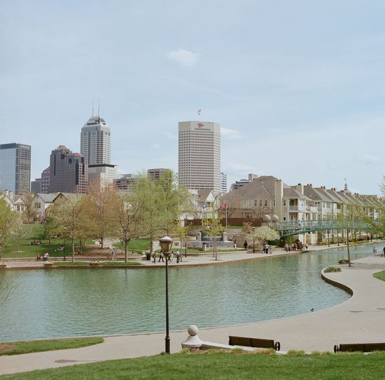 White River Canal with skyline in Indianapolis, Indiana. Architecture Building Building Exterior Built Structure Capital Cities  City City Life Cityscape Cloud Cloud - Sky Day Film Photography Grass MidWest Modern No People Outdoors River Sky Summer Tall - High Travel Destinations Tree Urban Skyline Water