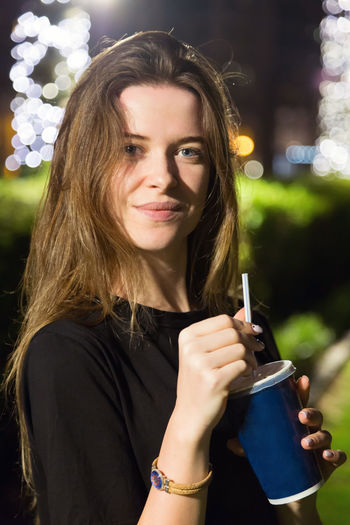 Portrait of a beautiful young woman drinking water