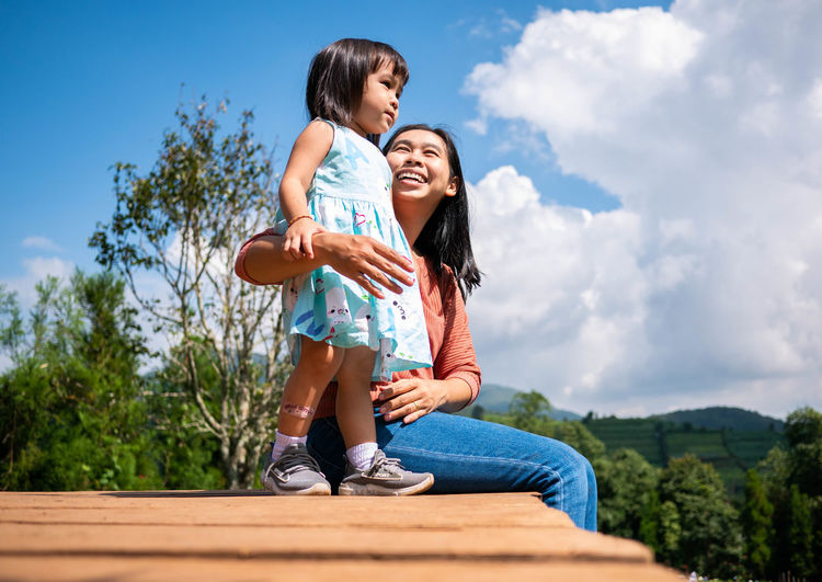 Smiling woman and daughter against sky