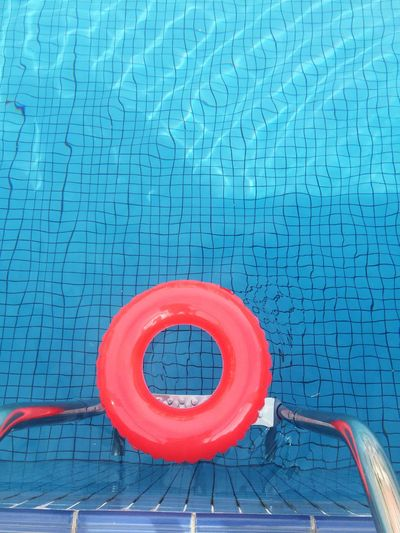 Directly Above Shot Of Red Inflatable Ring In Swimming Pool