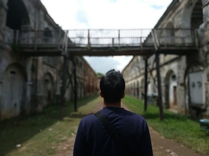 Rear view of man standing on bridge