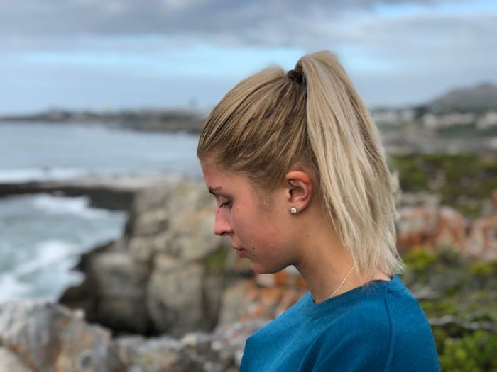 Side view of thoughtful young woman by sea