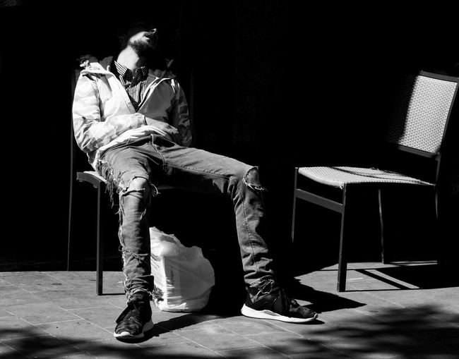 Snooze. Sleeping London_streetphotography Malephotographerofthemonth The Street Photographer - 2018 EyeEm Awards Streetphotography Streetphoto_bw LONDON❤ Street Photography Black And White Black Background Full Length Men Sitting Chair Close-up Shadow Human Leg Long Shadow - Shadow