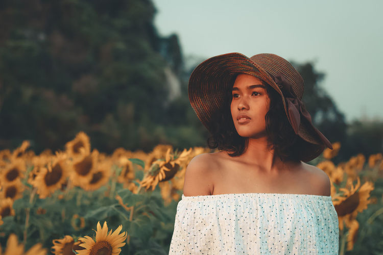 Woman In Hat Standing Against Flowering Sunflowers