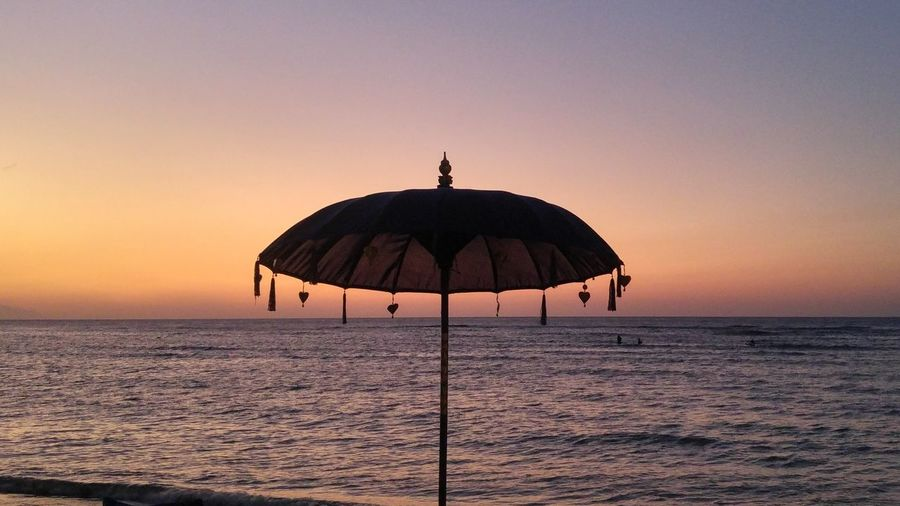 Silhouette lifeguard hut in sea against clear sky during sunset
