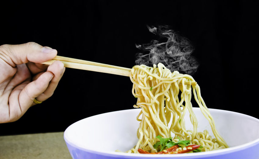 Cropped image of person having spaghetti with chopsticks against black background
