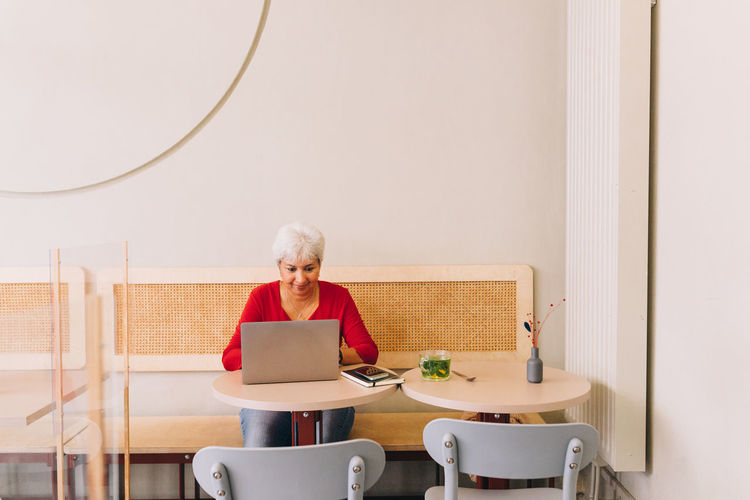 Full length of woman sitting on chair at table