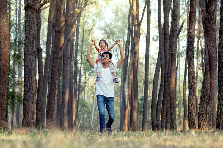 Surface level view of father carrying daughter in forest