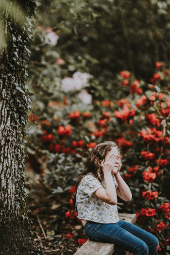 Girl Sitting On Bench While Covering Face Against Plants