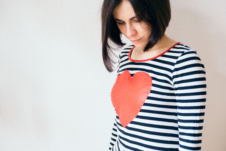 Woman With Heart Shape On T-Shirt Against White Background