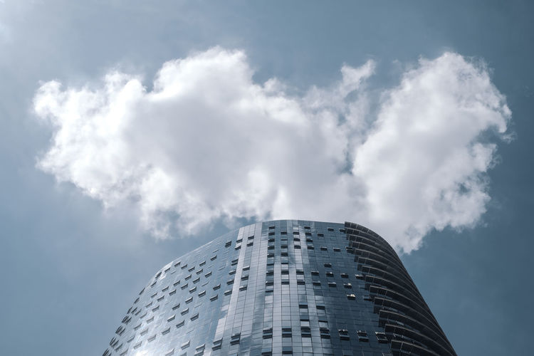 Low angle view of modern building against clouds in the sky