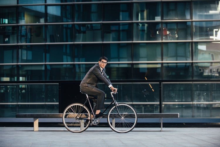 Man riding bicycle on glass building in city
