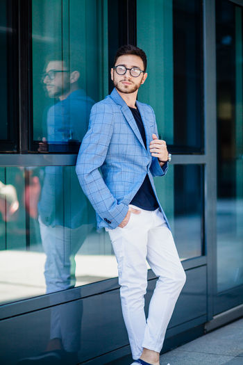 Young Businessman in Urban area Building Exterior Casual Clothing Clothing Day Front View Glass - Material Glasses Lifestyles Looking At Camera One Person Outdoors Portrait Real People Reflection Smiling Standing Three Quarter Length Transparent Window Young Adult