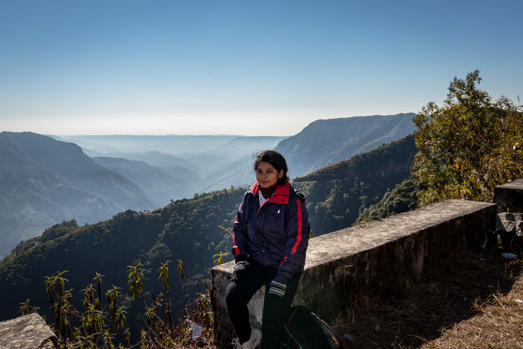 Full length of woman sitting against mountain and sky