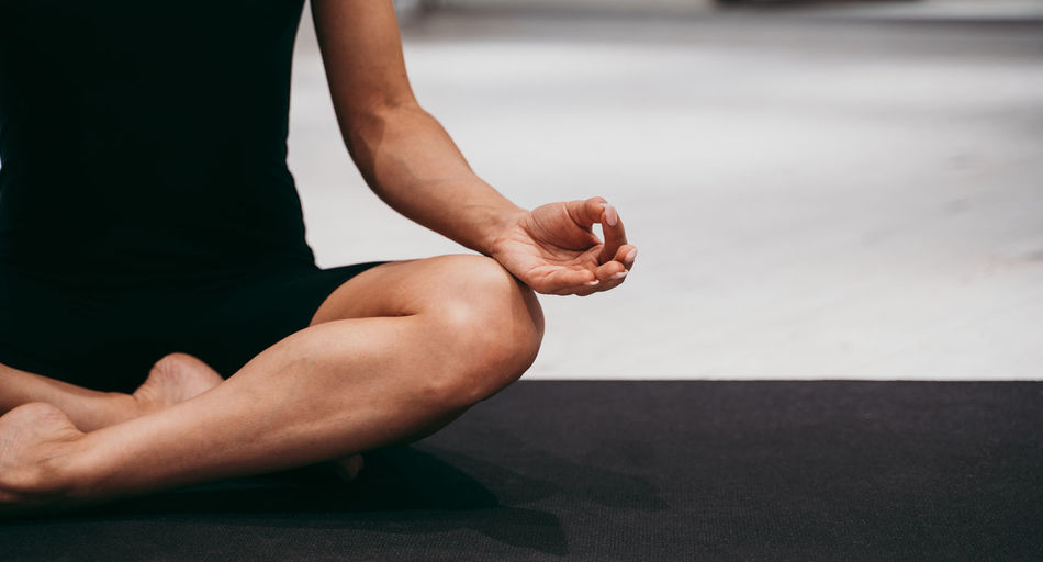 Low section of woman meditating at gym