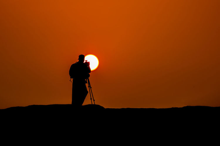 Silhouette man photographing against orange sky