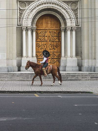 Mexican man with traditional clothes riding a horse in the city