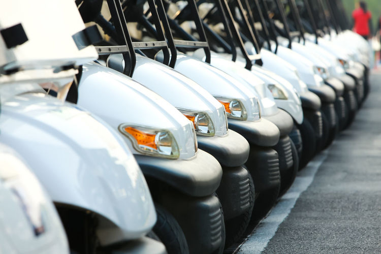 Golf cars or golf carts in a row outdoors on a sunny spring day In A Row Transportation Mode Of Transportation Car Land Vehicle Motor Vehicle Wheel Day Repetition Selective Focus No People Outdoors Focus On Foreground Tire Side By Side Sport Close-up Order Parking Auto Racing