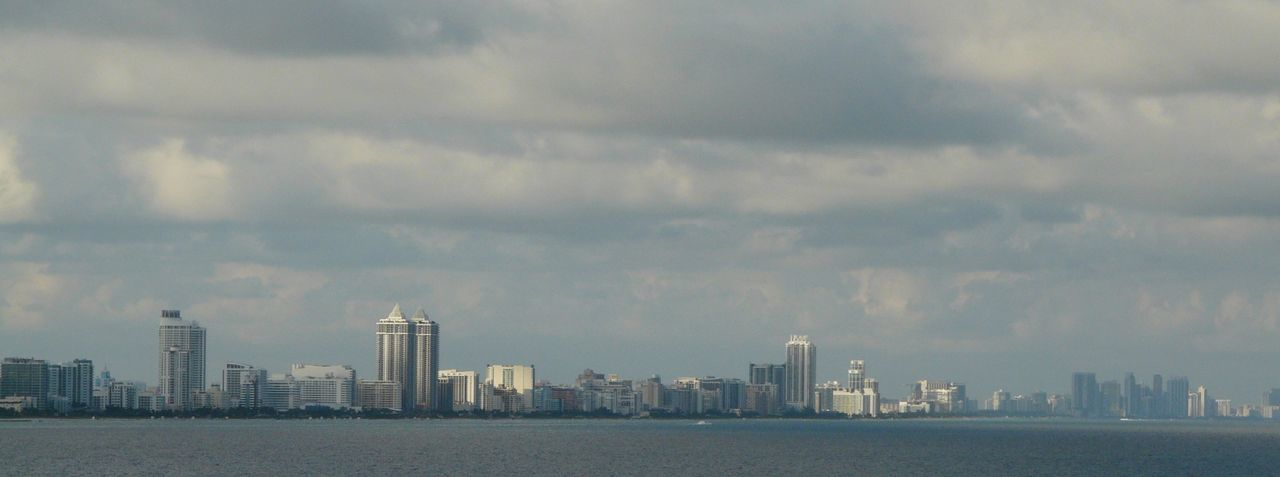 Sea And Buildings Against Cloudy Sky In City
