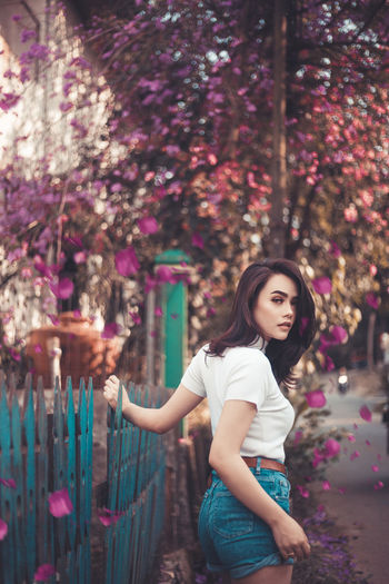 Portrait Of Young Woman Standing By Fence Against Trees At Park