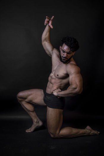 Shirtless man kneeling against black background