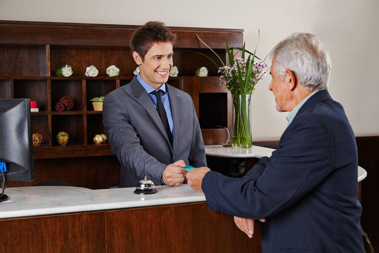 Smiling receptionist talking to customer at luxury hotel