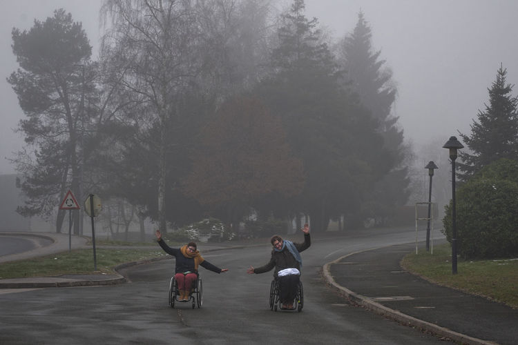 People riding motorcycle on road against trees