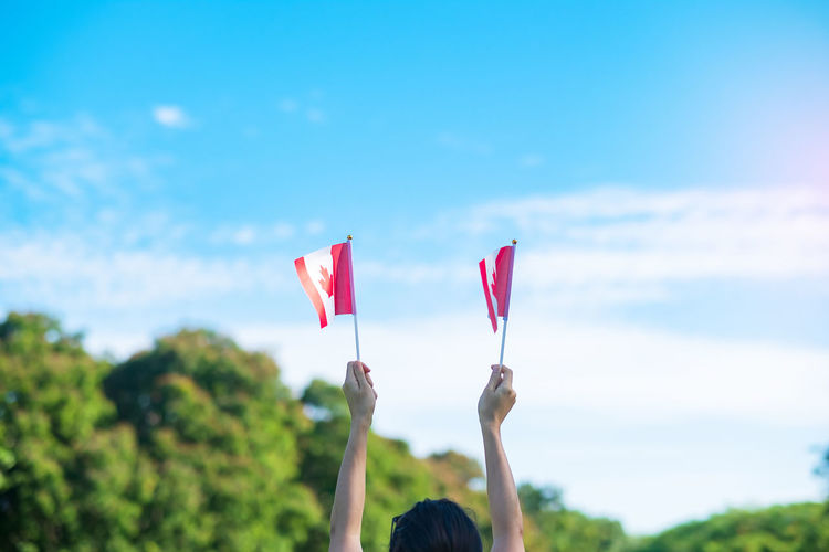 Person holding flag against sky